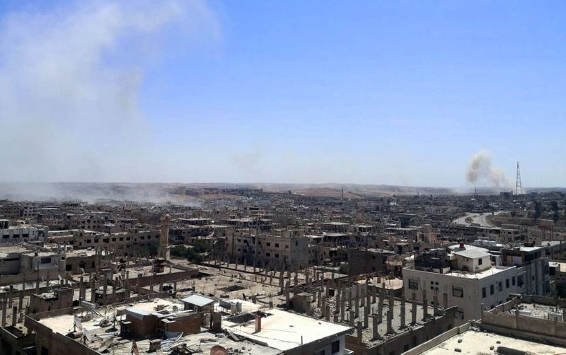 A view shows damaged buildings as smoke rises in Deraa