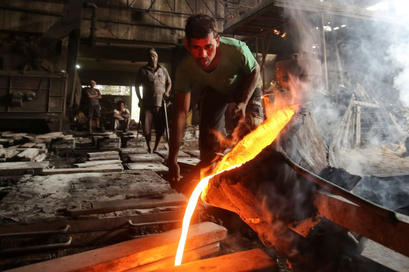 FILE PHOTO: A worker pours molten iron from a ladle to make automobile spare parts inside an iron casting factory in Ahmedabad