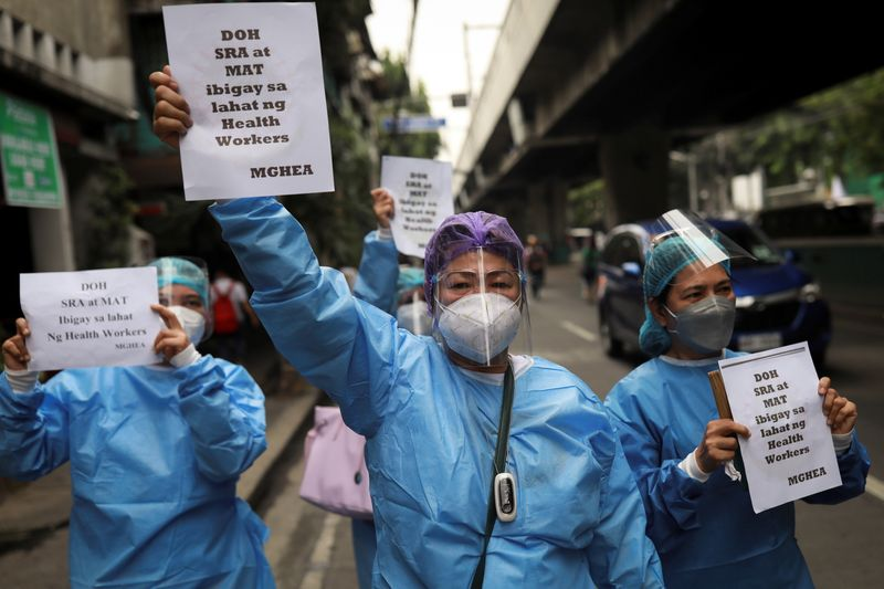 Healthcare workers protest outside the Department of Health in Manilla