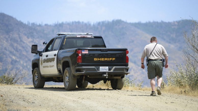 A Mariposa County deputy sheriff stands watch over a remote area northeast of the town of Mariposa, Calif., near the area where a family and their dog were reportedly found dead the day before. (Craig Kohlruss/The Fresno Bee via AP)