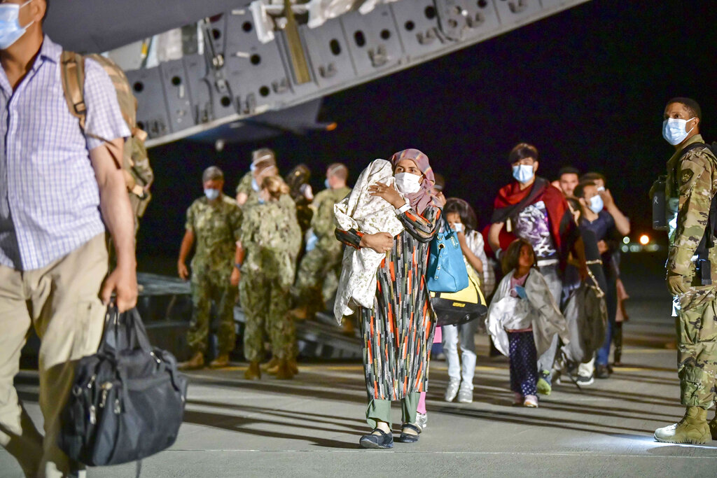 CORRECTS PHOTOGRAPHER TO DANIEL YOUNG - Evacuees from Afghanistan disembark from an Air Force C-17 Globemaster III at the Sigonella U.S. air base in Sicily, southern Italy, Sunday, Aug. 22, 2021. People fleeing Afghanistan arrived at the U.S. naval air base in Sicily as Washington tried to ramp up evacuations following the Taliban takeover of the country by using overseas military bases as temporary transit points. (Daniel Young/U.S. Navy via AP)