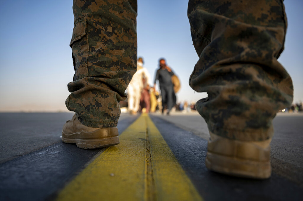 In this image provided by the U.S. Air Force, a U.S. Marine provides security for evacuees boarding a U.S. Air Force C-17 Globemaster III at Hamid Karzai International Airport in Kabul, Afghanistan, Tuesday, Aug. 24, 2021. (Senior Airman Taylor Crul/U.S. Air Force via AP)