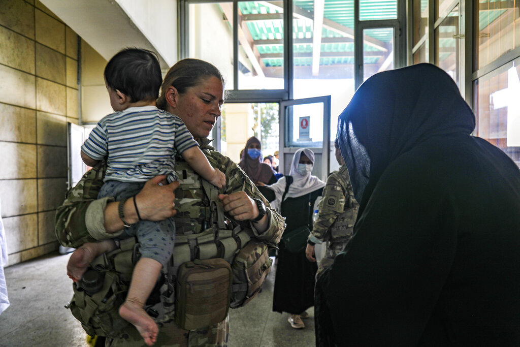 In this image provided by the U.S. Army, a medical officer assigned to the 82nd Airborne Division speaks with an Afghan woman and helps her with her child during ongoing non-combatant evacuation of U.S. civilian personnel, Special Immigrant Visa applicants, and other at-risk individuals, at Hamid Karzai International Airport, Kabul, Afghanistan, Wednesday, Aug. 25, 2021. (Sgt. Jillian G. Hix/U.S. Army via AP)
