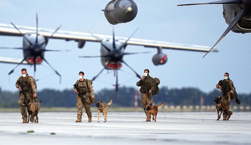 German Soldiers arrive with dogs on a plane from Tashkent, Uzbekistan at the Bundeswehr airbase in Wunstorf, Germany, Friday, Aug. 27, 2021, after they finished the evacuation mission in Kabul, Afghanistan. (AP Photo/Martin Meissner)