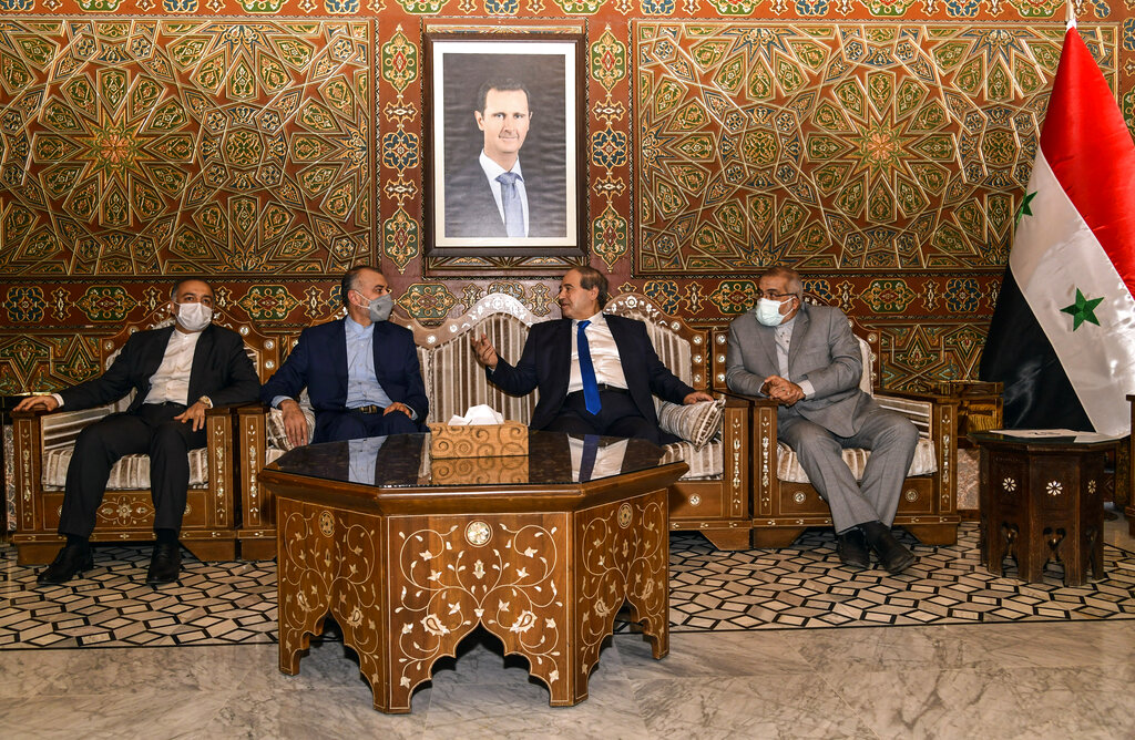"""In this photo released by the Syrian official news agency SANA, Syria's Foreign Minister Faisal Mekdad, second right, receives Iran's new Foreign Minister Hossein Amir-Abdollahian, second left, in Damascus, Syria, Sunday Aug. 29, 2021. Mekdad said Sunday that the """"thunderous defeat"""" by the United States in Afghanistan will lead to similar defeats for American troops in Syria and other parts of the world. (SANA via AP)"""