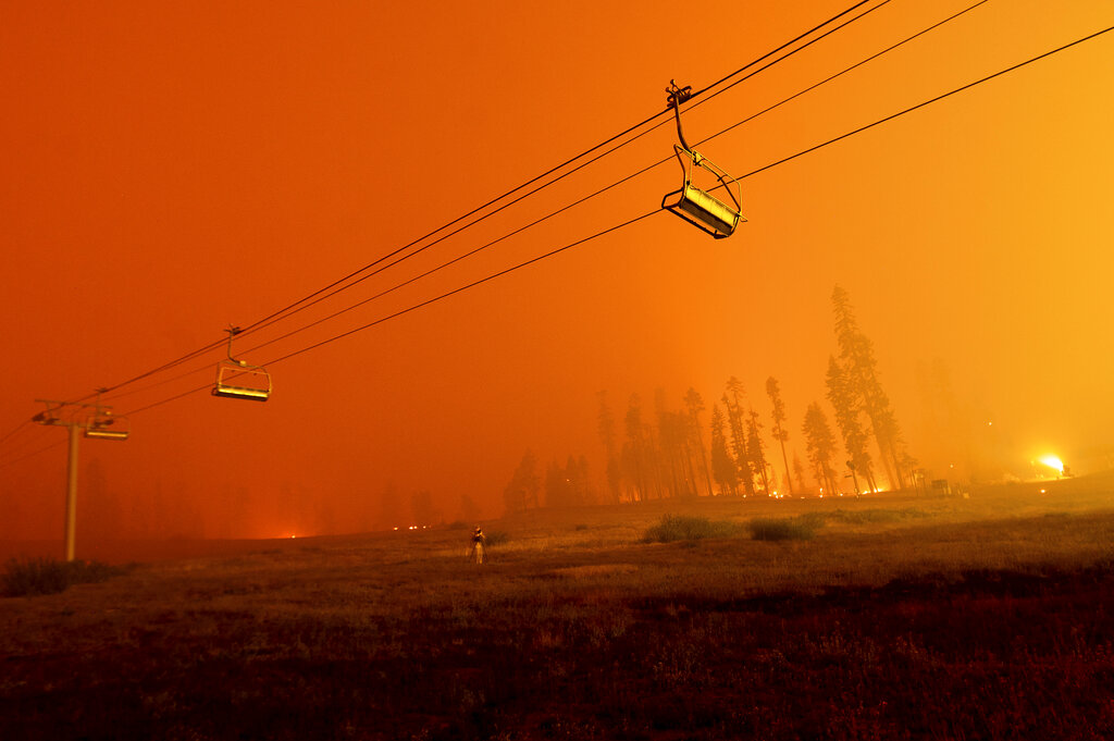 Seen in a long camera exposure, the Caldor Fire burns as chairlifts hang at the Sierra-at-Tahoe ski resort on Monday, Aug. 30, 2021, in Eldorado National Forest, Calif. The main buildings at the ski slope's base survived as the main fire front passed. (AP Photo/Noah Berger)