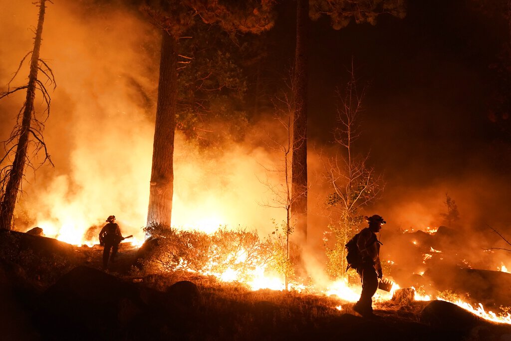 Two firefighters monitor the Caldor Fire burning near homes in South Lake Tahoe, Calif., Monday, Aug. 30, 2021. As the winds returned this week, the Caldor Fire roared over the Sierra crest and bore down on the southern end of Lake Tahoe. (AP Photo/Jae C. Hong)