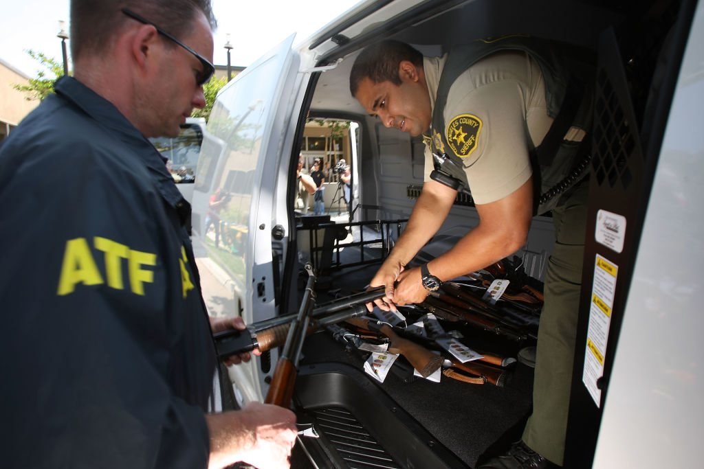 LAKEWOOD, CA - MAY 21: Officers load some of about 125 weapons confiscated during what the federal authorities say is the largest gang takedown in United States history into a van after a press conference to announce the arrests of scores of alleged gang members and associates on federal racketeering and drug-trafficking charges on May 21, 2009 in the Los Angeles-area community of Lakewood, California. 147 people are indicted in the case involving racially motivated attacks on African-Americans and law enforcement officers. Operation Knockout is the latest of several investigations that found gangs engaged in race-based violence. Two years ago, a Latino gang was charged with waging a violent campaign to drive blacks out of a Los Angeles-area neighborhood that resulted in 20 homicides. Last year, another Latino gang was accused of targeting blacks and killing 14-year-old Cheryl Green, whose death became a community rallying point. In 2006, Avenues gang members Latinos were convicted of assaults and killings of blacks in the 1990s. (Photo by David McNew/Getty Images)
