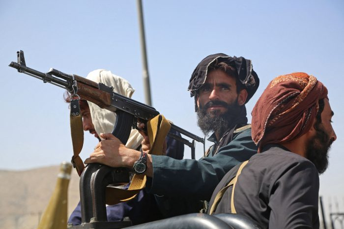Taliban fighters stand guard in a vehicle along the roadside in Kabul. (Photo by -/AFP via Getty Images)