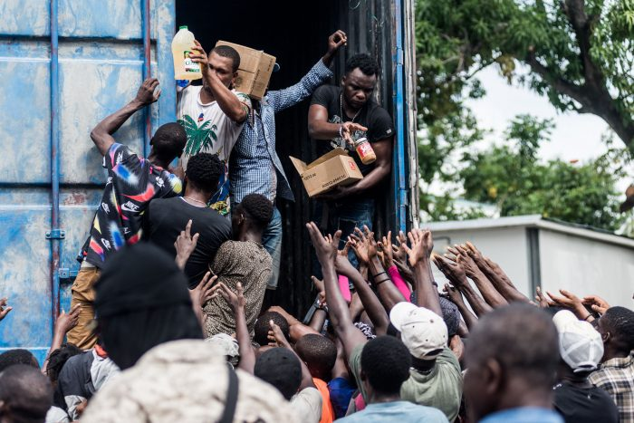 """Men hand out supplies to a crowd of earthquake victims during the distribution of food and water at the """"4 Chemins"""" crossroads in Les Cayes, Haiti. (Photo by REGINALD LOUISSAINT JR/AFP via Getty Images)"""