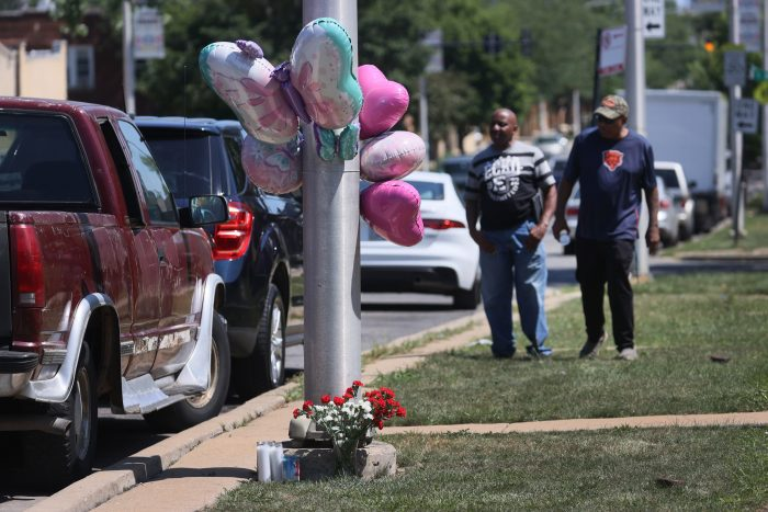 Dr. Bishop Rich Tolefree. left, and Andrew Tolefree look at a small makeshift memorial that sits along the road near the site where their grandnieces were shot after leaving their grandmother's home yesterday in Chicago, Illinois. (Photo by Scott Olson/Getty Images)