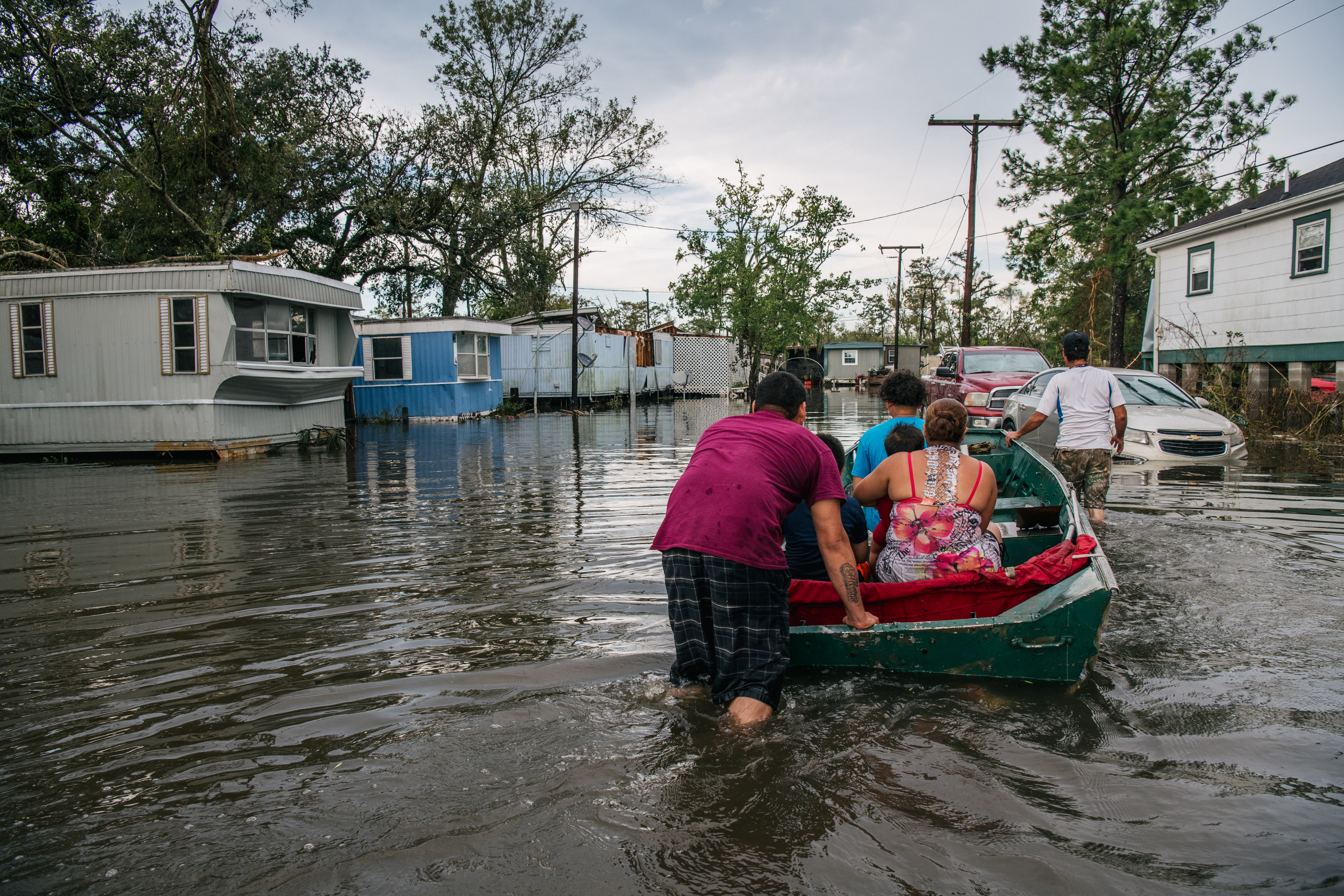 The Maldonado family travel by boat to their home after it was flooded during Hurricane Ida on August 31, 2021 in Barataria, Louisiana. (Photo by Brandon Bell/Getty Images)