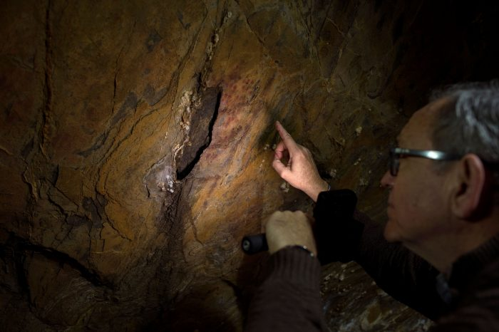 Pedro Cantalejo, director of the Andalusian cave of Ardales, looks at Neanderthal cave paintings inside the cavern. (JORGE GUERRERO/AFP via Getty Images)