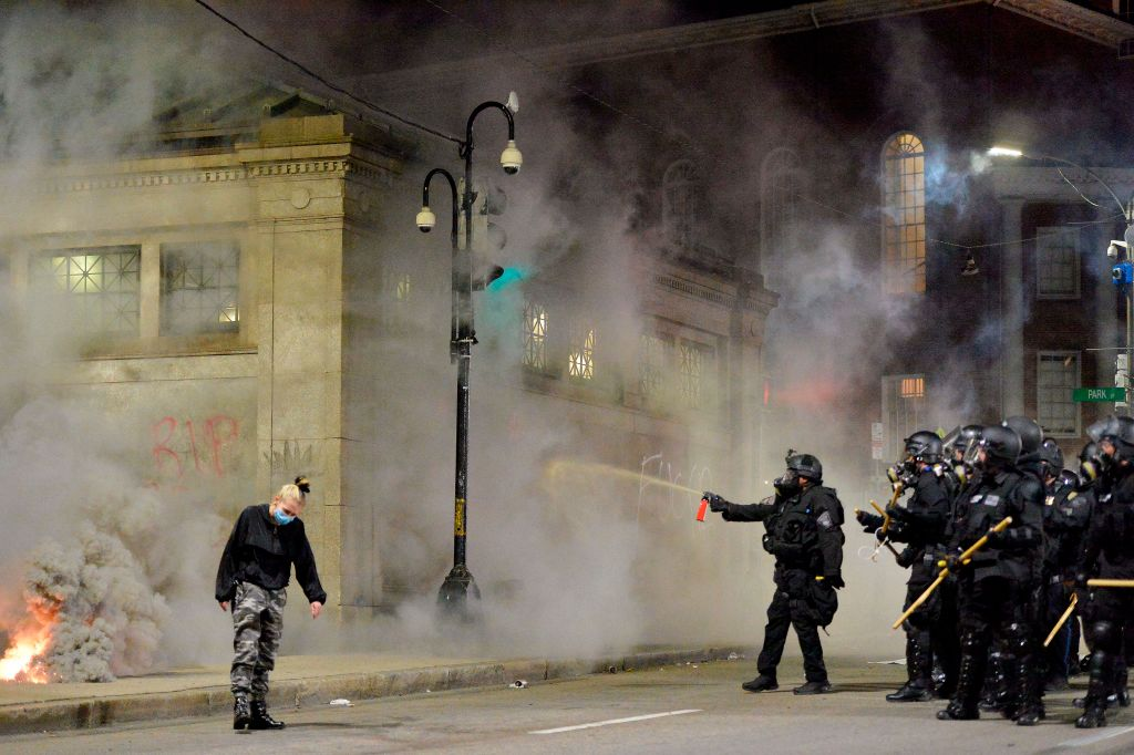 Police shoot pepper spray toward a protester during a demonstration over the death of George Floyd, an unarmed black man who died in Minneapolis Police custody, in Boston, Massachusetts on May 31, 2020. - Authorities imposed curfews in the capital Washington and other major US cities on May 31 to prevent fresh rioting after anti-racism protestors again took to the streets to voice their fury at police brutality. (Photo by Joseph Prezioso / AFP) (Photo by JOSEPH PREZIOSO/AFP via Getty Images)