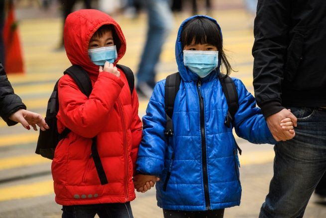 Children wearing face masks cross a road during a Lunar New Year of the Rat public holiday in Hong Kong on January 27, 2020, as a preventative measure following a coronavirus outbreak which began in the Chinese city of Wuhan. (Photo by Anthony WALLACE / AFP) (Photo by ANTHONY WALLACE/AFP via Getty Images)