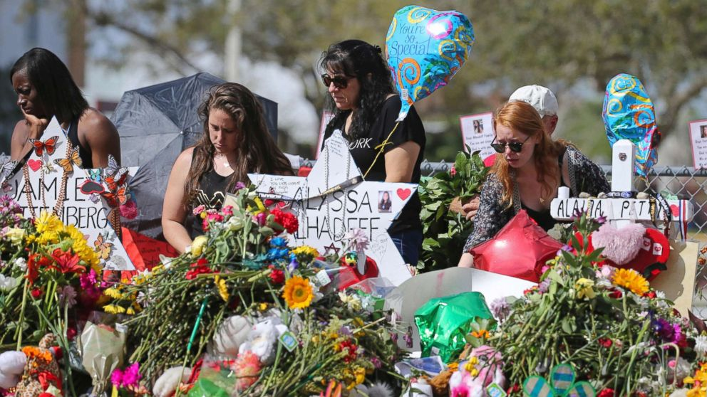 Mourners bring flowers as they pay tribute at a memorial for the victims of the shooting at Marjory Stoneman Douglas High School, Feb. 25, 2018, in Parkland, Fla.