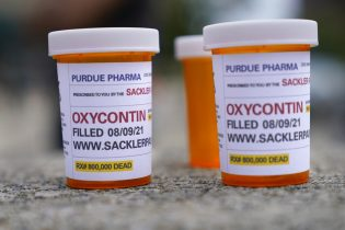 Fake pill bottles with messages about Purdue Pharma are displayed during a protest outside the courthouse where the bankruptcy of the company is taking place in White Plains, N.Y., Monday, Aug. 9, 2021. Purdue Pharma's quest to settle thousands of lawsuits over the toll of OxyContin is entering its final phase with the grudging acceptance of most of those with claims against the company. (AP Photo/Seth Wenig)