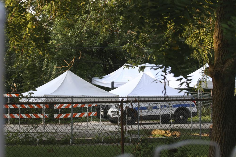"""A police car and tents sit in the backyard of a home following a report that two bodies may be buried there in suburban Lyons, Ill., Friday, Aug. 27, 2021. Authorities are planning to excavate the suburban Chicago backyard Friday after two adult brothers found living in what police called a """"hoarder home"""" said they had buried the bodies of their mother and sister there. (Antonio Perez/Chicago Tribune via AP)"""