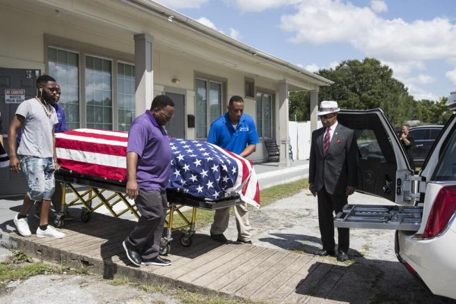 The body of New Orleans Police detective Everett Briscoe is placed into a hearse before it is escorted from the Respect for Life Funeral Home for the journey back to New Orleans, in Houston. (Brett Coomer/Houston Chronicle via AP)