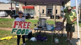 Joyce and Dave Thomas offer free jambalaya, cooked up by one of their neighbors, along the Carrollton streetcar tracks in New Orleans. Much of the city was without power and many restaurants and individuals were trying to help the community with free food. (AP Photo/Kevin McGill)