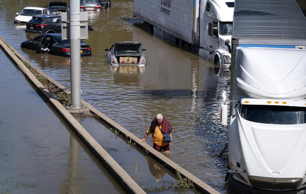 A person who eventually waded to a truck, moves amongst cars and other trucks that are stranded by high water Thursday, Sept 2, 2021, on the Major Deegan Expressway in Bronx borough of New York as high water left behind by Hurricane Ida still stands on the highway hours later. (AP Photo/Craig Ruttle)