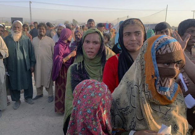 Afghan families gather to receive food stuff distributing by an Islamabad-based Christian organization on the outskirts of Chaman, a border town in the Pakistan's southwestern Baluchistan province. (AP Photo)