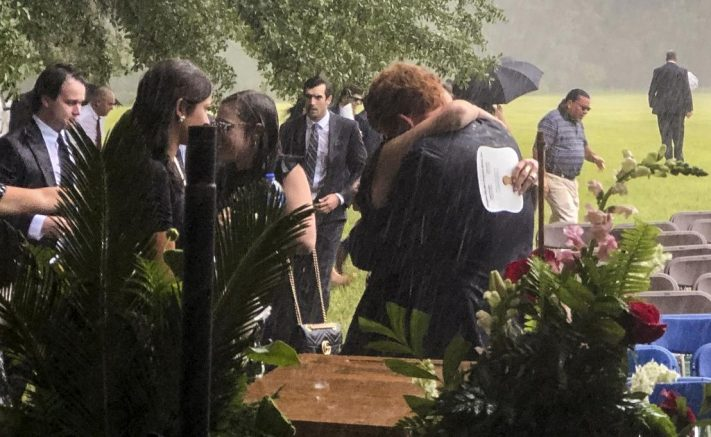 Buster Murdaugh, center, receives a hug in the rain during the funeral service for his brother, Paul, and mother, Maggie, on Friday, June 11, 2021 in Hampton, S.C. State police say information gathered by agents investigating the death of the mother and son from the prominent South Carolina legal family has led them to review a nearby unsolved hit-and-run death from six years ago. (Kacen Bayless/The Island Packet via AP)