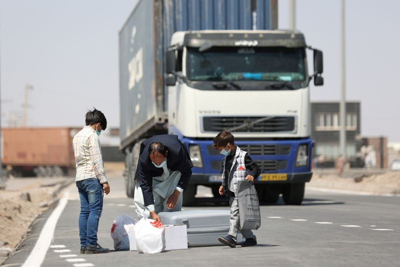 FILE PHOTO: Afghan nationals enter Iran at the Dowqarun border crossing between Iran and Afghanistan
