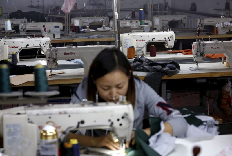 A woman works in a small-sized factory producing clothes and hats, in which more than half of its production line has stopped its operation because of a downturn in its business at the Qingyundian industrial zone in Beijing