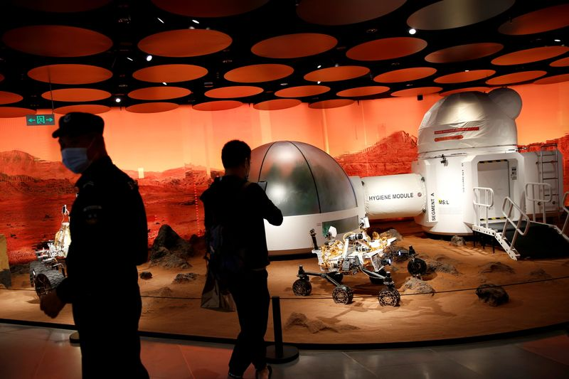 FILE PHOTO: People wearing face masks following the COVID-19 outbreak are seen near models of a Mars base and a rover displayed inside the SKP-S shopping mall in Beijing