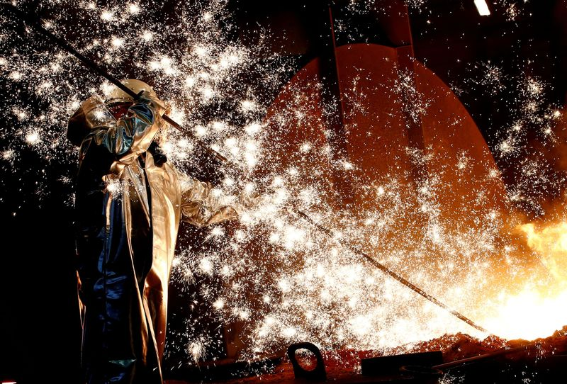FILE PHOTO: A steel worker of Germany's industrial conglomerate ThyssenKrupp AG stands a mid of emitting sparks of raw iron from a blast furnace at Germany's largest steel factory in Duisburg