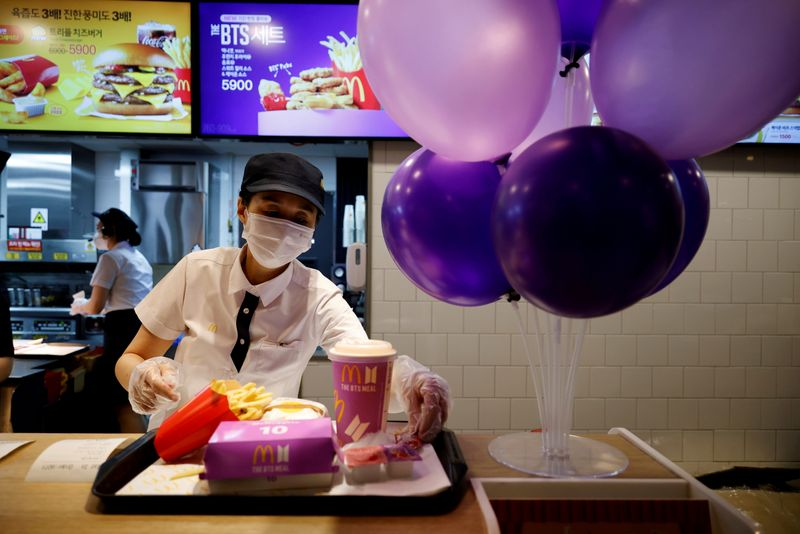 FILE PHOTO: FILE PHOTO: An employee of McDonald's serves a BTS meal, which is inspired and promoted by K-pop boy band BTS, during lunch hour at its restaurant in Seoul