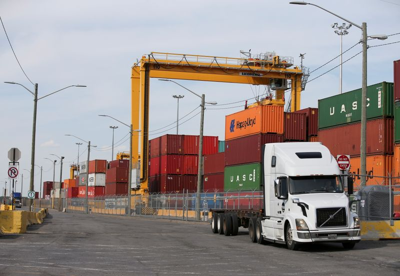 FILE PHOTO: A truck moves past stacked shipping containers at the Port of Montreal