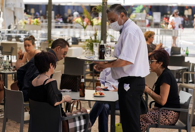 A waiter tends to customers on the terrace at a commercial district in Madrid