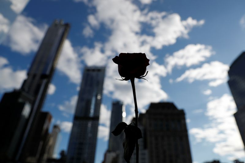 A flower seen in silhouette stands on the south reflecting pool at the 9/11 Memorial site in the lower section of Manhattan, New York City