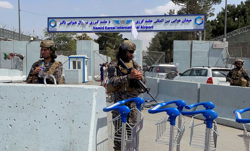 FILE PHOTO: Taliban forces stand guard at the entrance gate of Hamid Karzai International Airport a day after U.S troops withdrawal in Kabul