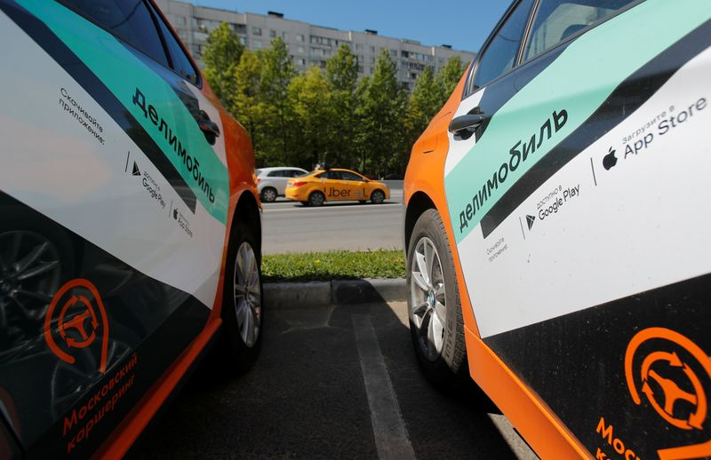 Taxi car drives by Delimobil branded vehicles amid the outbreak of the coronavirus disease (COVID-19) in Moscow
