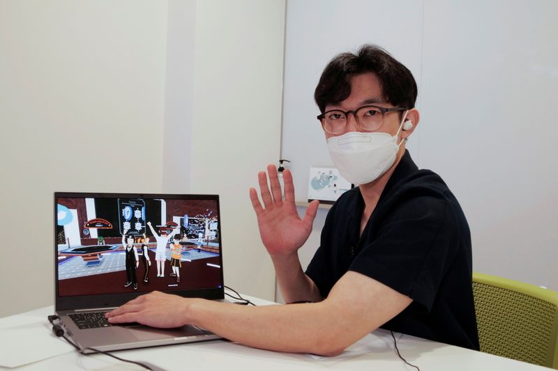 Shaun poses for photographs with a laptop showing his avatar in Decentraland in Seoul