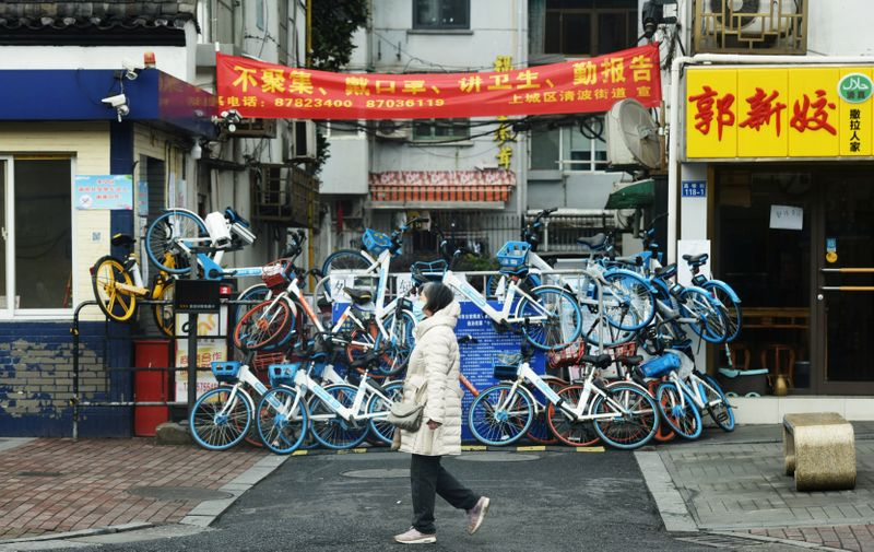 Woman wearing a face mask walks past an entrance to a residential compound that has been blocked by shared bicycles, as the country is hit by an outbreak of the novel coronavirus, in Hangzhou