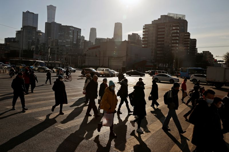 People cross a street during morning rush hour in front of the skyline of the CBD in Beijing