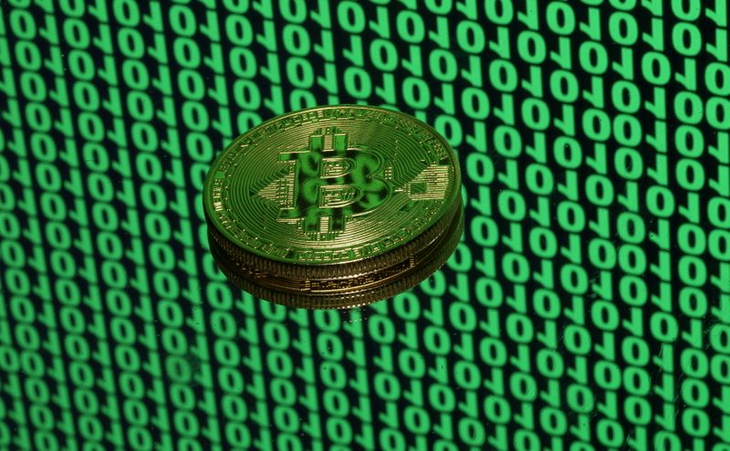 FILE PHOTO: Bitcoin token is seen placed on a monitor that displays binary digits in this illustration picture