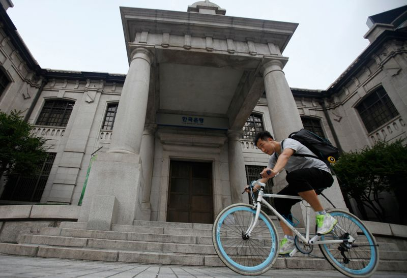 A man gets on a bicycle in front of the Bank of Korea in Seoul