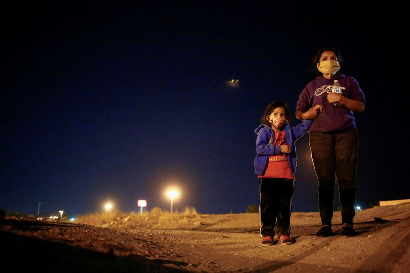 An asylum-seeking migrant from Honduras and her daughter are seen before crossing the Rio Bravo river to turn themselves in to U.S Border Patrol agents to request for asylum in El Paso, Texas, U.S., in Ciudad Juarez