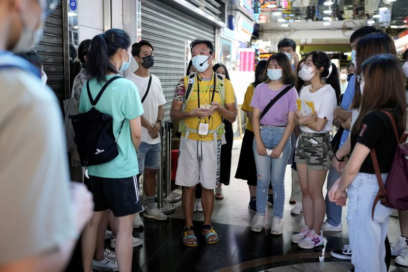 Tour guide Michael Tsang talks to tourists during a tour of refugee communities in Hong Kong