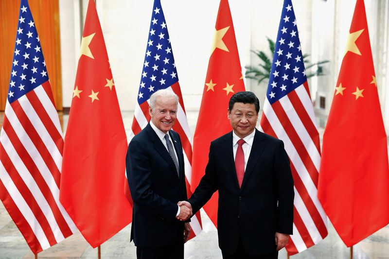 FILE PHOTO: Chinese President Xi Jinping shakes hands with US Vice President Joe Biden inside the Great Hall of the People in Beijing