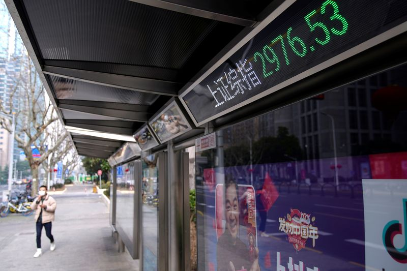 A men wearing a mask walk by an electronic board showing the Shanghai and Shenzhen stock indexes in Shanghai