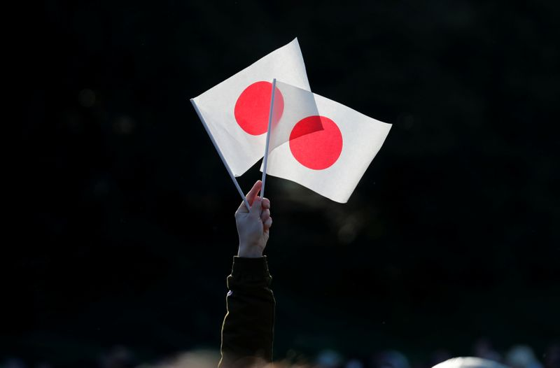 A well-wisher holds Japan's national flags during Emperor Naruhito's public appearance for New Year celebrations at the Imperial Palace in Tokyo