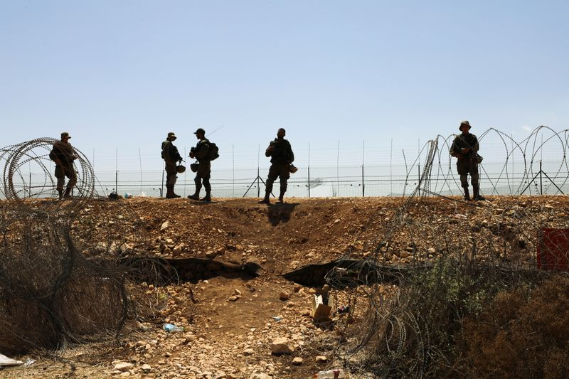 Israeli soldiers stand guard along a fence leading to the Israeli-occupied West Bank, as part of search efforts to capture six Palestinian men who escaped from Gilboa prison in northern Israel earlier this week