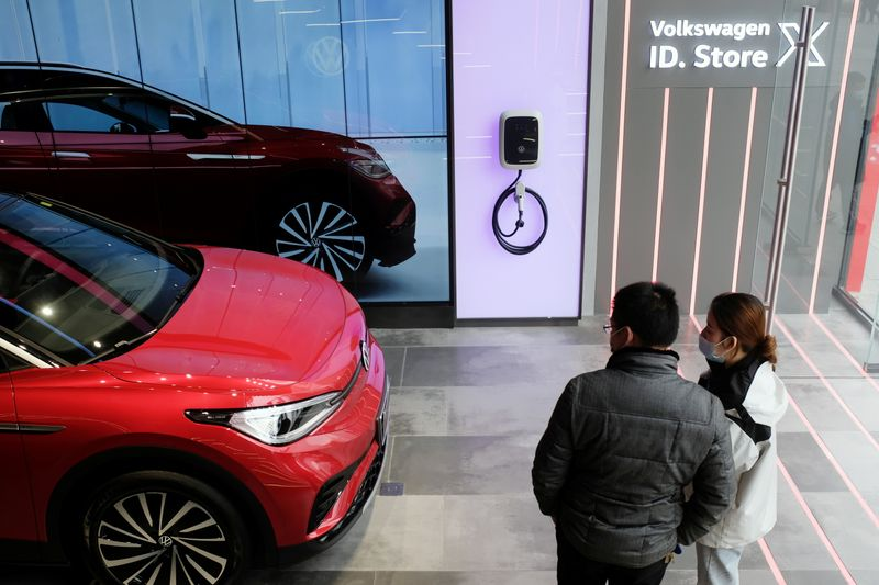 FILE PHOTO: People check a Volkswagen ID.4 X electric vehicle inside an ID. Store X showroom of SAIC Volkswagen in Chengdu