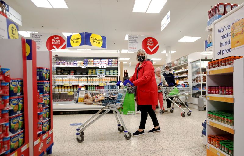 FILE PHOTO: A woman wearing a face mask pushes a shopping cart at a Tesco supermarket in Hatfield, Britain